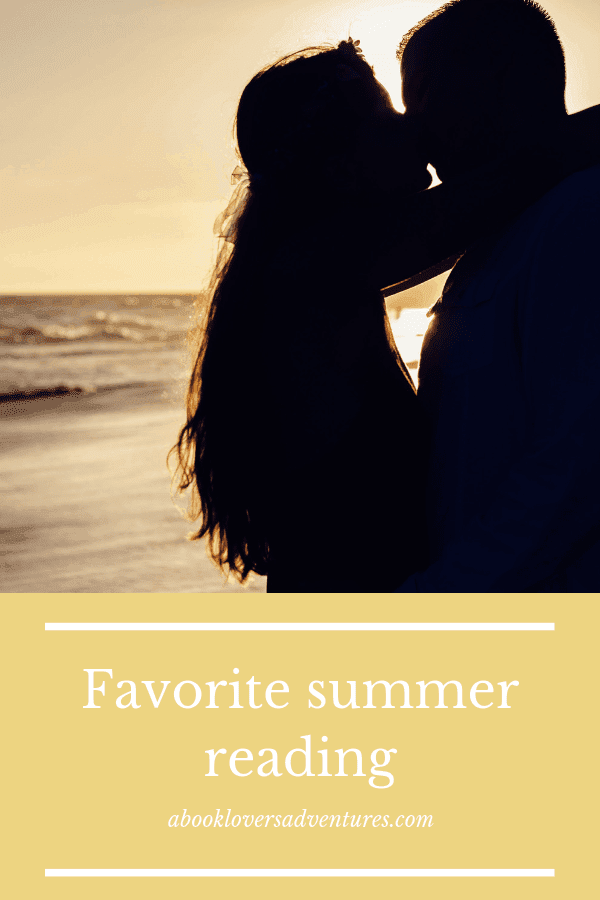 couple on beach at sunset - what genre do you read during the summer?