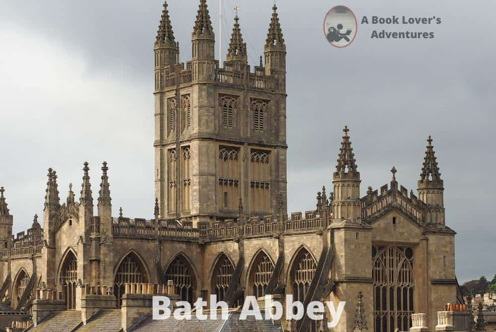 Exterior of the Bath Abbey, a cross shaped stone building with a center spire. Very gothic looking. Great spot to visit on your Day Trip to Bath