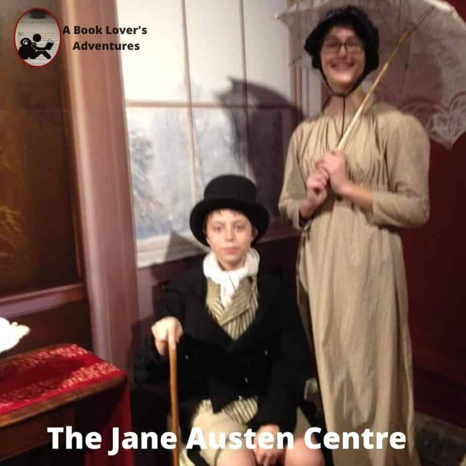 Girl with plain dress and parasol and boy with top hat, vest, short jacket and cane. Dressed up at the Jane Austen Centre during our Day Trip to Bath