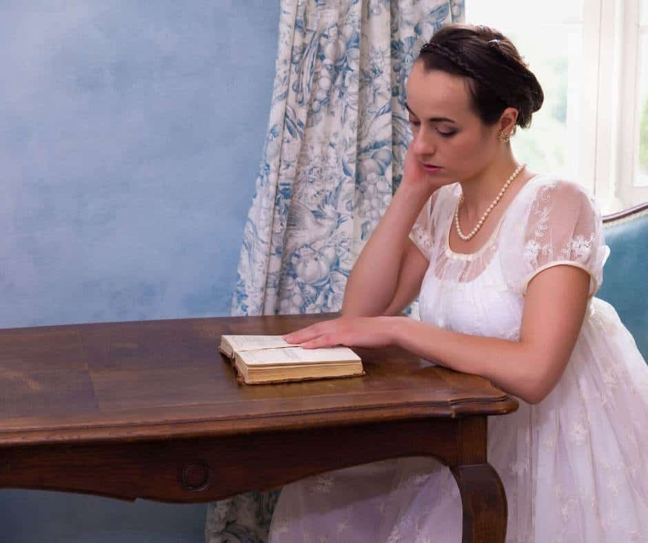 Woman in regency dress reading at a table; Jane Austen experience