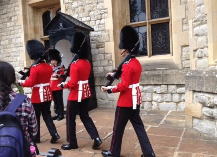 red coated British guards marching away; black hats and black pants